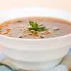 Barley beef soup in a white bowl with a spoon on the side. Very shallow depth of field.