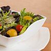 Mixed green salad meal in a white bowl. Shallow depth of field.