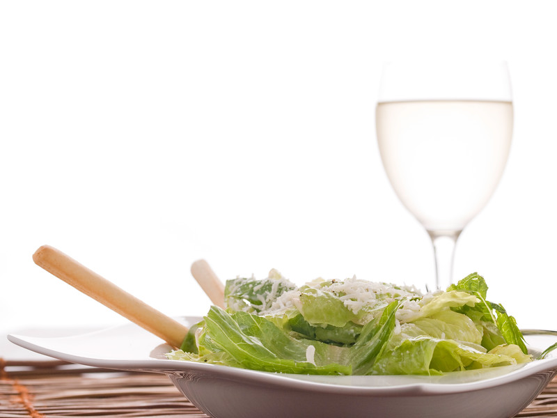 ceasar salad on a white plate with a white wine glass with a lot of copyspace