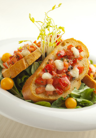 Bruschetta in a white bowl with salad.