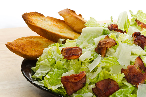Fresh caesar salad in a plate with sliced baked bread and big bacon piece. Large depth of field.