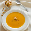 Pumpkin soup cream with seeds and spoon on the side.