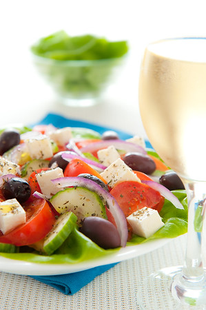 Fresh and healthy greek salad with white wine. Shallow depth of field.
