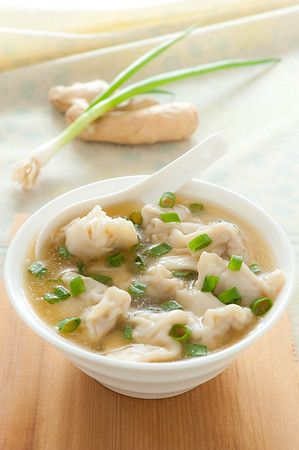 Wonton soup with spoon in a bowl. Traditional asian food. Shallow depth of field.