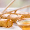 healthy vegetable spring rolls on a white plate with sauce.Very shallow depth of field.