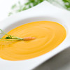 carrot cream on white served on a white bowl with a carrot vegetable on it.Shallow depth of field