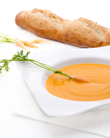 carrot cream on white served on a white bowl with a carrot vegetable on it.Fresh bread on background.
