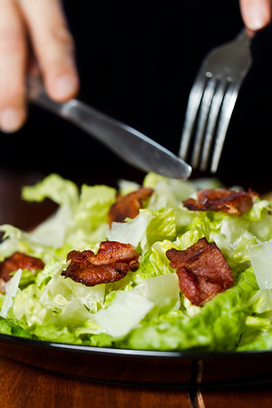 Somebody eating a fresh caesar salad in a plate with big piece of bacon on it. Very shallow depth of field.