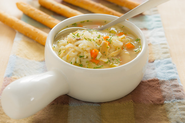 Healthy chicken rice soup with spoon. Shallow depth of field.