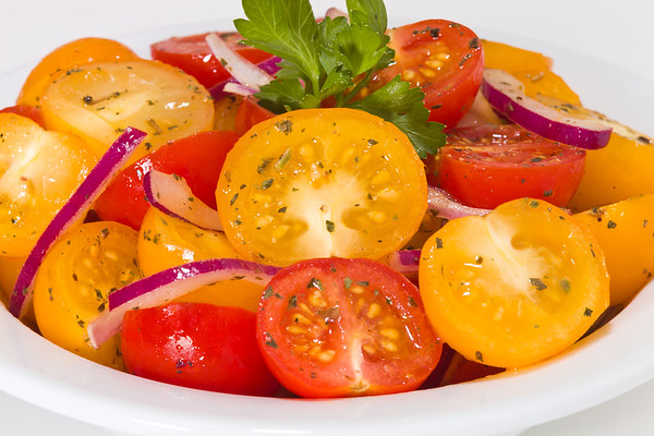appetizer salad with cherry tomato red and yellow in a white bowl.