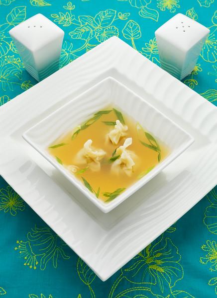 Won ton soup in a white bowl.