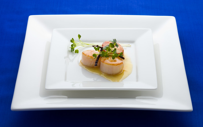 Scallop seafood appetizer with vanilla stick and sauce.