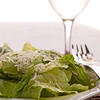 ceasar salad on a white plate with a white wine glass