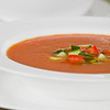 Cold soup called gaspacho in white dishware. Focus is on tomato and cucumber piece. Very shallow depth of field.