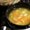 chicken soup with cutted bread on a black background. Focus on the soup with very shallow depth of field.