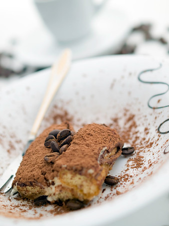 tiramisu dessert on white with espresso cup.Very shallow depth of field.