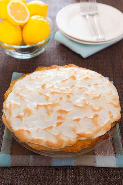 Whole homemade citrus pie with fruit and plate in the background. Focus on the meringue with shallow depth of field.