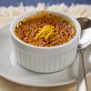 creme brulee desert on white plate with a spoon. French culture cuisine.