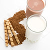 chocolate milk with cocoa and rolled wafers on a white background