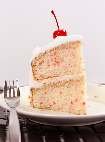 beautiful vanilla piece cake with cherry on the top.Shallow depth of field.