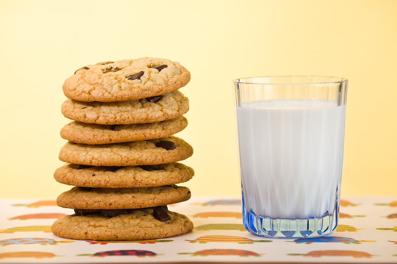 Butter cookie stacked with chocolate chip and milk on the side. Very shallow depth of field.