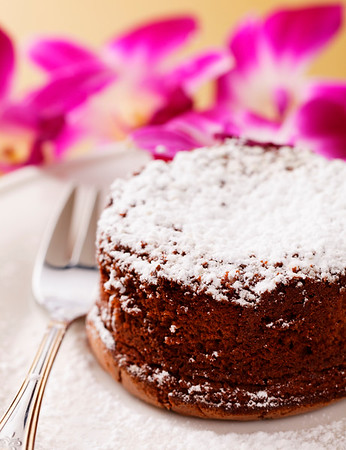 molten chocolate cake with orchid flower in the background. Very shallow depth of field.