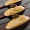 Whipped coffee mousse in a dark chocolate spoon. Very shallow depth of field. focus on the bean.