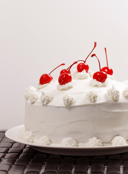 beautiful vanilla cake with cherry on the top.