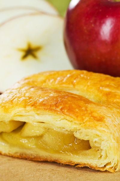 Apple turnover with fruit in the background. Very shallow depth of field.