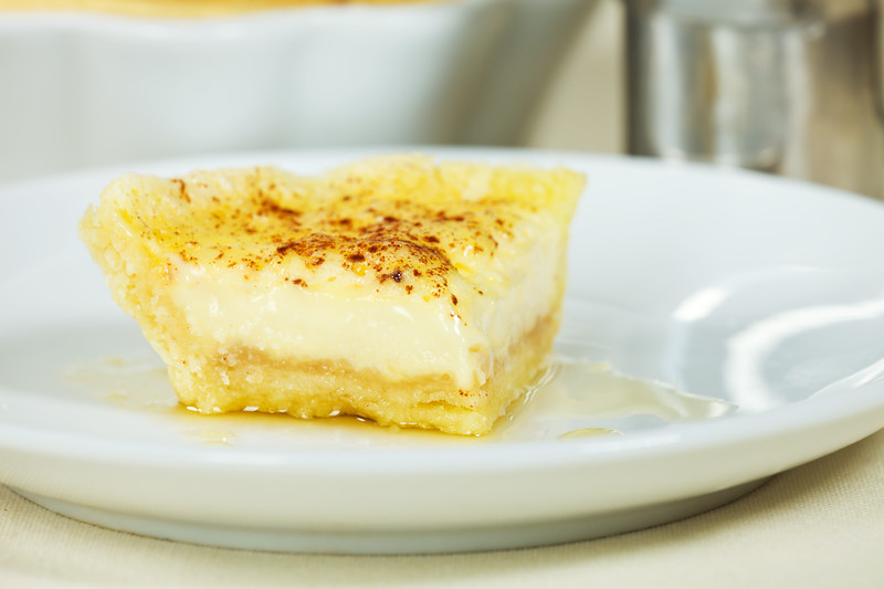 Open pie or flan portion with sugar cream flavor. Very shallow depth of field.