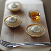 mini maple syrup tart on a wooden board with a fork.Focus on the first portion. Shallow depth of field.