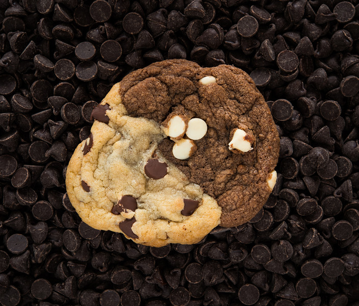 One homemade sweet cookie isolated on chocolate chips background.