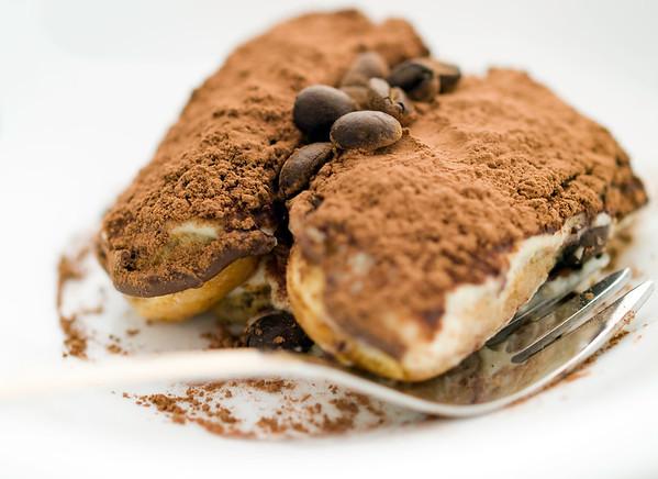 tiramisu dessert on a white plate. Very shallow depth of field