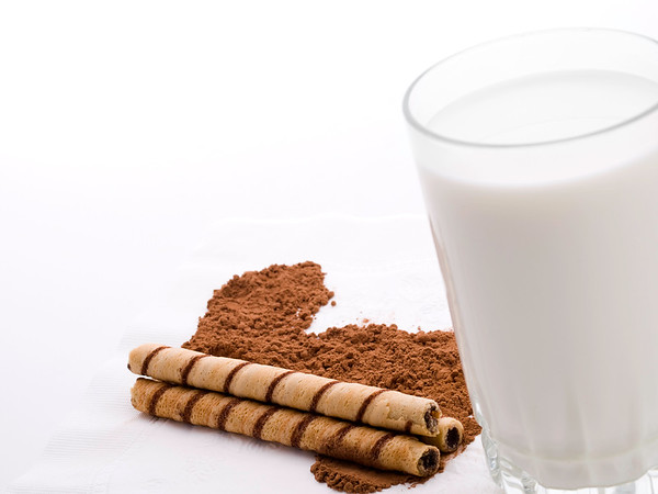 rolled wafers with cocoa and milk on a white background