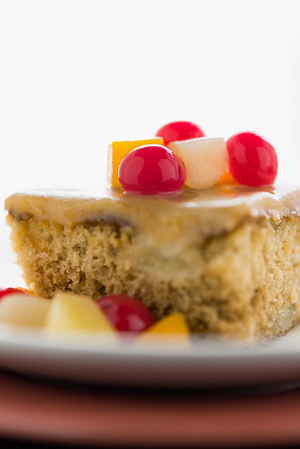 Fruit Cake dessert with cherry,peach and orange. White background and very shallow depth of field.
