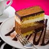 Creamy chocolate mousse cake on a white plate with a pink background. Added vignetting and very shallow depth of field.