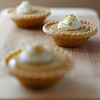 mini maple syrup tart on a wooden board with a fork. Focus on the middle portion.Shallow depth of field.