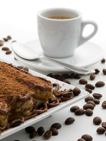 tiramisu dessert on white with coffee grain and espresso cup