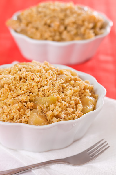 Apple crumble dessert in a bowl with a fork on the side. Shallow depth of field.