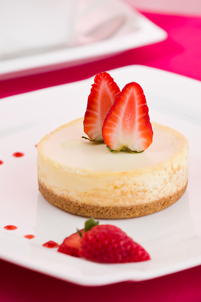 Strawberry cheese cake on a white plate. Shallow depth of field.