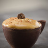Whipped coffee mousse in a dark chocolate cup. Very shallow depth of field.Focus on the bean.