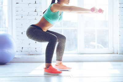 Burn in buttocks. Side view of young woman in sportswear doing squat and holding dumbbells while standing in front of window at gym