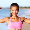 Happy sporty fitness woman flexing muscles on beach. Smiling young is wearing pink sports bra. Femal