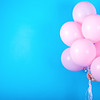 Girl hand holding pink air balloons on blue background free space for text. Pink birthday balloons with copy space for text. Love happiness birthday valentine concept. Happy holiday pink balloons