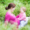 Laughing Young Pregnant Mother Playing With Her One Year Old Baby Daughter In A Blooming Garden