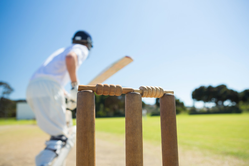 Close up of wooden stump by batsman standing on field against clear sky
