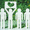 Paper people on green grass on bright background. Greenpeace a symbol of the heart from the grass. Love and protection of nature and ecology.