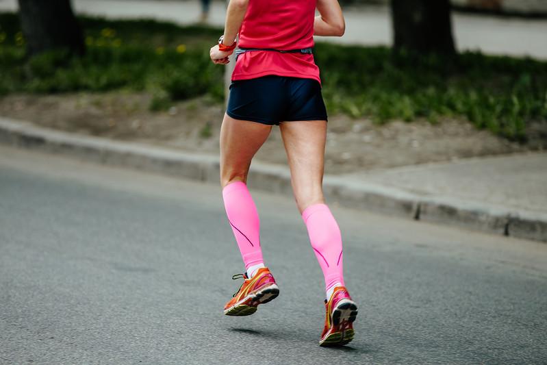 back runner girl in pink compression socks running street of city