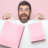 Christmas and birthday. Hipster with present package on pink background. Guy with happy face and gift pack. Man with long beard with pink shopping bag. Holiday celebration and black friday shopping.