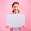 Cheerful beautiful asian young woman holding blank board on pink background.